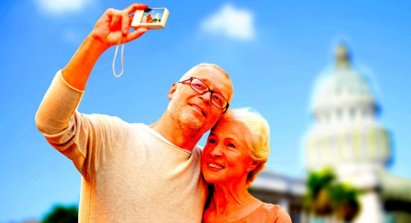age, tourism, travel, technology and people concept - senior couple with camera taking selfie on street over washington white house background